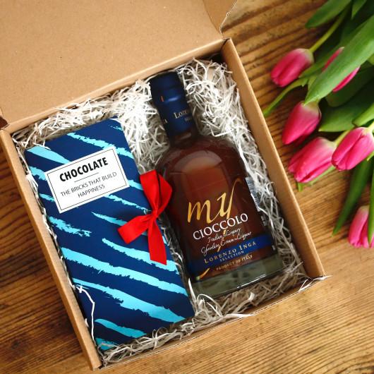 kartonska darilna škatla, v kateri je čokoladni liker in čokolada v modrem zavitku s pentljo, na desni šopek roza tulipanov