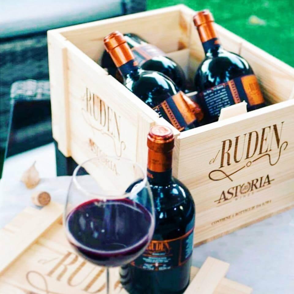 Lesena vinska škatla s steklenicami vina Astoria in kozarec rdečega vina